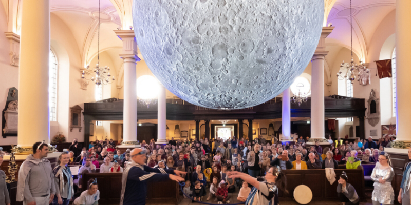Crowd of families under giant hanging sculpture of the moon